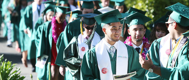 Group of ethnically diverse Napa Valley Students wearing green graduation cap and gown.
